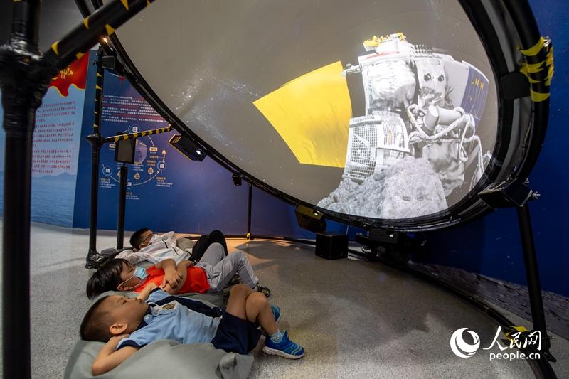 """全国科普日活动11日在全国各地启动。中国科技馆主会场内,几位小朋友在探月体验区沉浸式体验""""月球挖土""""过程。人民网记者 翁奇羽摄"""