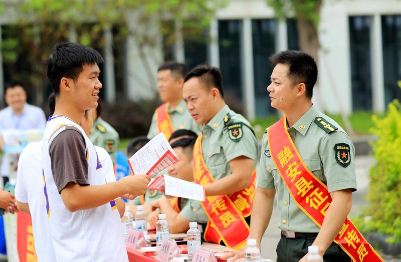 在广西柳州市融安县高级中学,征兵工作人员向学生宣传讲解征兵政策。谭凯兴摄